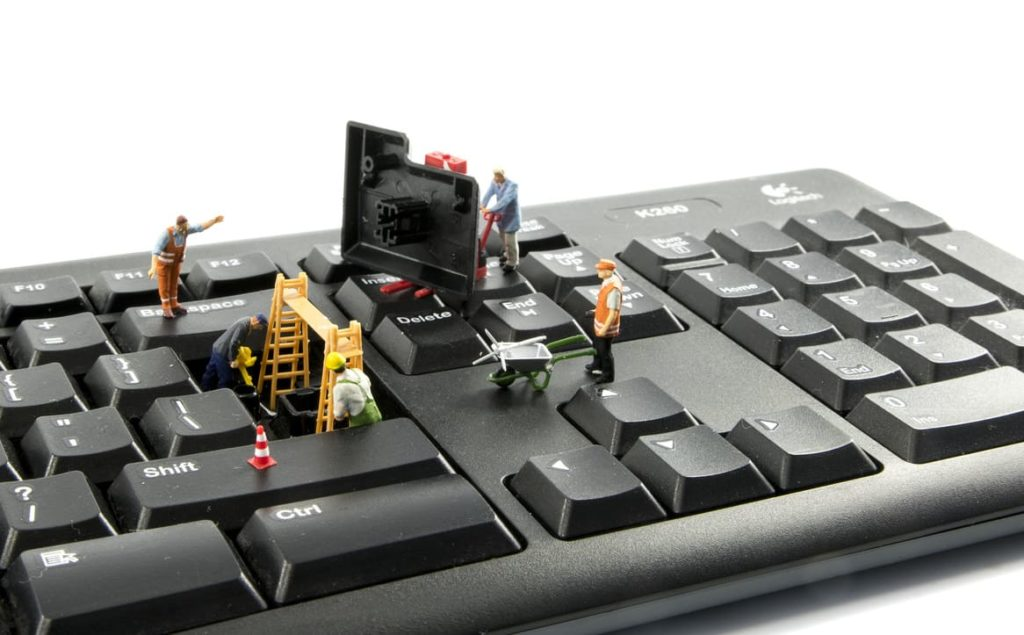 A keyboard being built by mini figurines