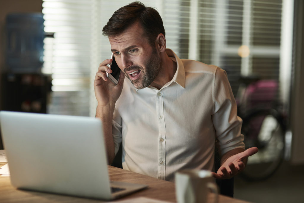 Angry businessman talking by mobile phone