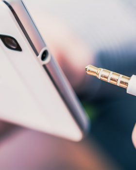 A Headphone Jack Of A White Mobile Phone Next To A Headset Cable